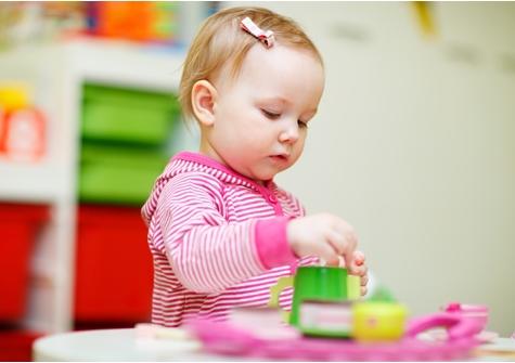 Een meisje speelt met blokjes aan een tafeltje.